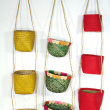 Spice-Carrier Baskets - Available in various colours and materials. On the photo : Yellow: raffia spice-carrier, 1,80 € (VAT not included) Green: aravola spice-carrier, 2,40 € (VAT not included) Red, hanging : raffia matting spice-carrier, 2,15 € (VAT not included) Red, on the floor : string spice-carrier, 3,00 € (VAT not included)